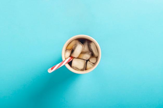 Verfrissende ijskoffie in een glas op een blauwe ondergrond. concept zomer, cola met ijs, verfrissende cocktail, dorst. plat lag, bovenaanzicht
