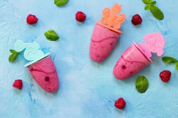 Verfrissende ijslolly's voor kinderen, frambozensorbet op blauwe betonnen ondergrond