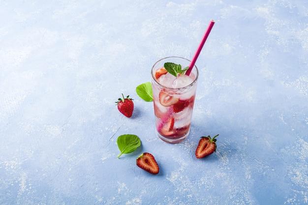 Verfrissende koele detoxdrank met aardbei en munt. zomer limonade of ijsthee in een glas. mojito cocktail met ijsblokjes. gezond eten.