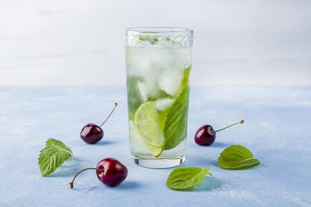 Verfrissende koele detoxdrank met limoen en munt. glas zomerlimonade of ijsthee versierd met kersen. mojito cocktail met ijsblokjes. gezond eten.