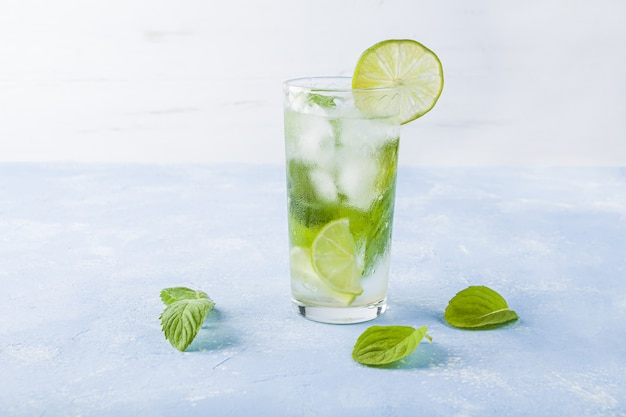 Verfrissende koele detoxdrank met limoen en munt. zomer limonade of ijsthee in een glas. mojito cocktail met ijsblokjes. gezond eten.