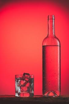 Verfrissende koude drank in fles met druppels en glas met ijs op rode oppervlak