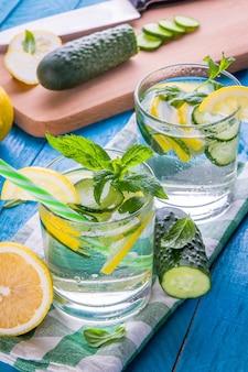Verfrissende limonade van citroen, komkommer, limoen en munt op blauwe achtergrond. zomers drankje. gezonde biologische dranken