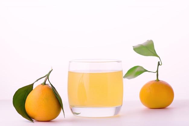 Verfrissende mandarijndrank in een glas met citrusvruchten op witte achtergrond