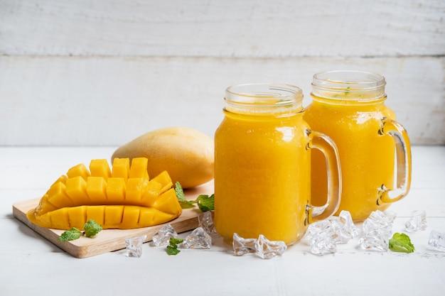 Verfrissende mango smoothies in glas met rijpe mango op witte houten tafel