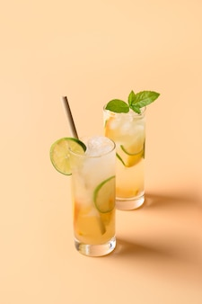 Verfrissende sinaasappel twee limonade met limoenplak op kleurenachtergrond. zomerdrankje.