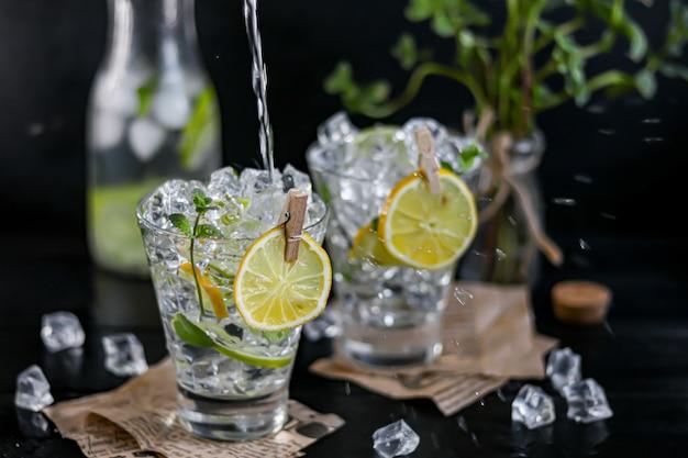 Verfrissende zomer alcoholische cocktail margarita met crushed ijs, limoen en munt als decoratie. wodka splash. op een donkere houten achtergrond. op de bladeren van de krant.