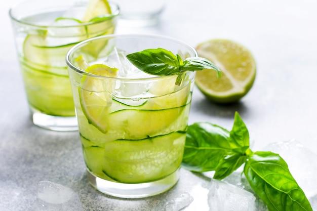Verfrissende zomer zelfgemaakte limonade gemaakt van limoen, citroen, komkommer en basilicum met ijs in glas op oude betonnen ondergrond. selectieve focus Premium Foto
