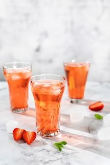 Verfrissende zomerdrank met aardbei in glazen op wit.