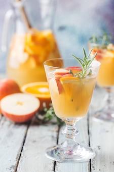 Verfrissende zomerdrank sangria of punch met fruit in een glas en pincher over houten