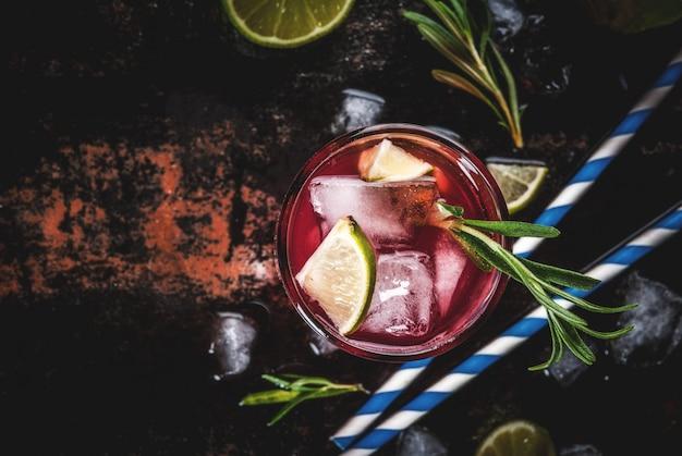 Verfrissing alcoholische rode cranberry en limoen cocktail met rozemarijn en ijs, twee glazen, donkere oppervlakte kopie ruimte bovenaanzicht