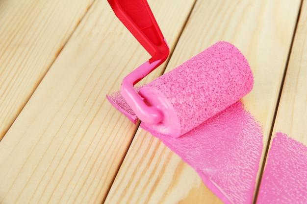 Verfrolborstel met roze verf, op houten
