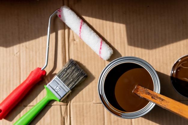 Verfroller in bak, kwasten en verfblik. gereedschappen voor het decoreren en renoveren van huizen