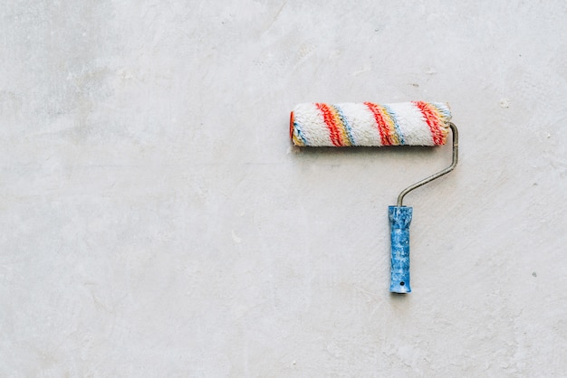 Verfroller met een blauw handvat geïsoleerd op betonnen vloer met ruimte voor tekst