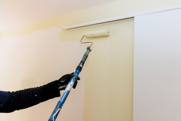 Verfrollerborstel met lange steel die kleurverf op de muur aanbrengt met huisrenovatie