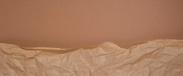 Verfrommeld ambachtelijk papier op een bruine kartonnen ondergrond. banier.
