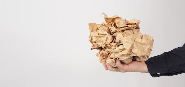 Verfrommeld bruin papier. het is verscheurd in de hand van de mens op een witte achtergrond.