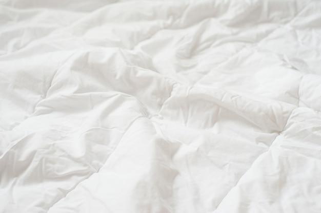 Verfrommeld dekbed witte deken textuur. detailopname.
