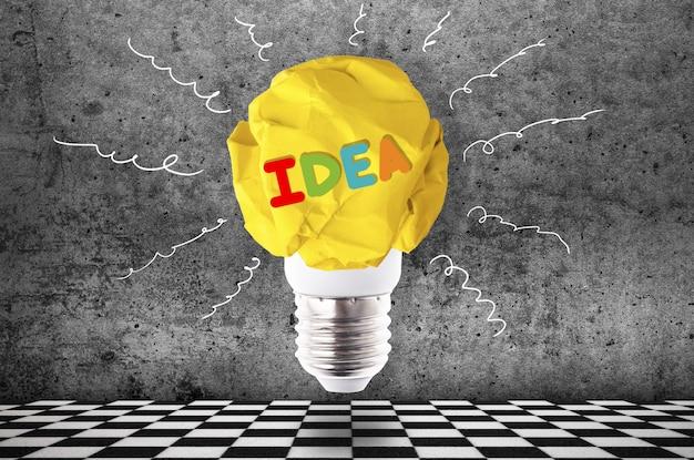 Verfrommeld geel papier gloeilamp met kleurrijke inscriptie idee, inspirerend beeld