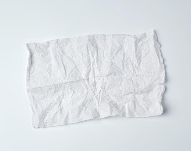 Verfrommeld gescheurd zacht wit vel keukenpapier met gekrulde hoeken