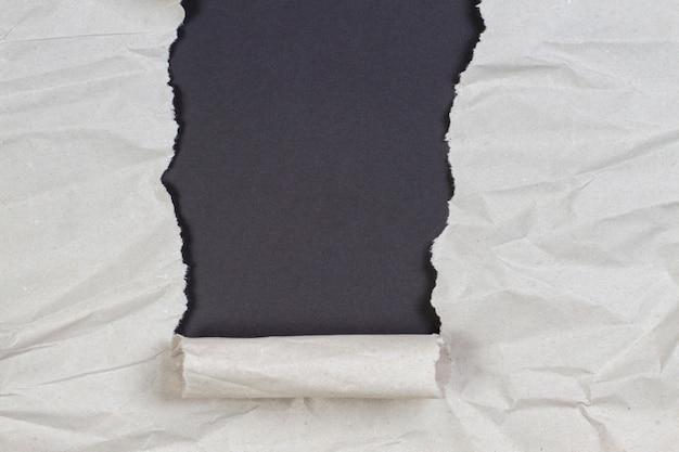 Verfrommeld pakketpapier gescheurd om zwarte achtergrond te onthullen met kopieerruimte