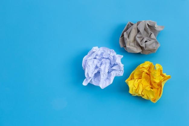 Verfrommeld papier ballen op blauwe muur.