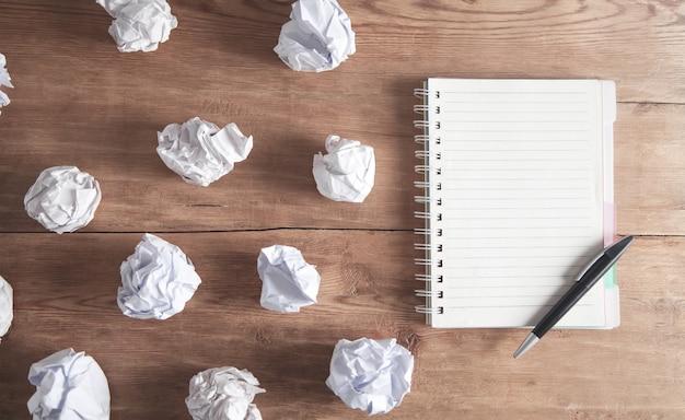 Verfrommeld papier met een blocnote en pen op het houten bureau.