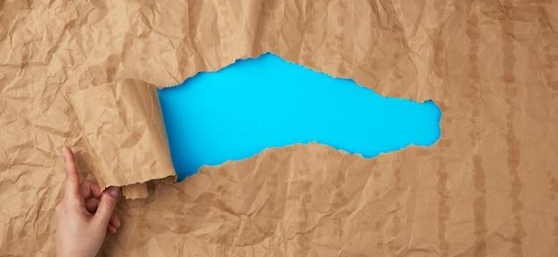 Verfrommeld papier textuur van een bruin vel papier met vettige vlekken en een groot gat