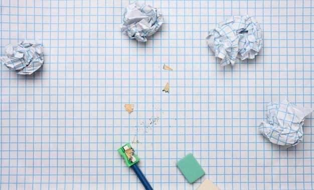 Verfrommeld papieren ballen en een geslepen houten potlood met schaafsel op een geruit vel papier
