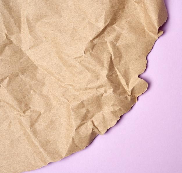 Verfrommeld vel bruin inpakpapier op een paarse achtergrond