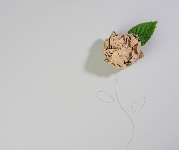 Verfrommeld vel bruin papier en een groen blad op een grijze achtergrond, vorm van een gloeilamp. energiebesparend concept, nieuw creatief idee, plat gelegd