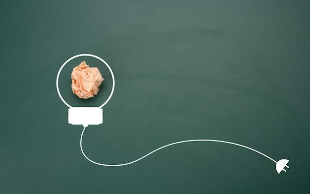 Verfrommeld vel papier op een groene achtergrond, vorm van een gloeilamp. energiebesparend concept, nieuw creatief idee, plat gelegd