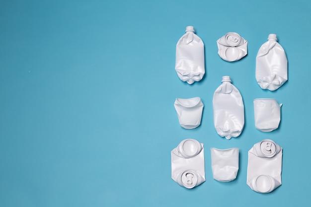 Verfrommelde plastic en metalen blikjes liggen op een blauwe muur met kopie ruimte. concept van zwerfvuil van het milieu en niet-rottend afval.
