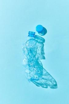 Verfrommelde plastic fles met schaduwen op een pastelblauwe muur. concept milieuvervuiling van plastic.