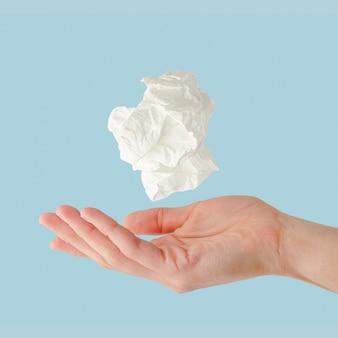Verfrommelde zakdoek die over vrouwelijke hand op blauw muur, gezondheidszorg en verkoudheidsconcept vliegen.