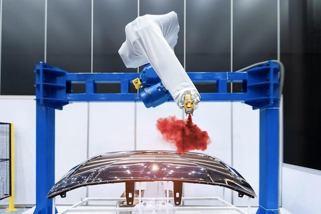 Verfspray met robotarm op het auto-onderdeel. hoogtechnologisch fabricageconcept.