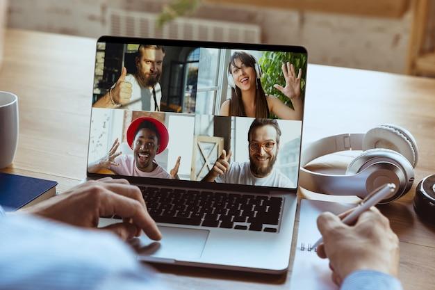 Vergadering op afstand. man aan het werk vanuit huis tijdens coronavirus of covid-19 quarantaine, extern kantoorconcept. jonge baas, manager voor laptop tijdens online conferentie met collega's en team.