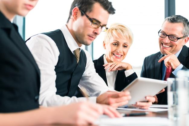 Vergadering op kantoor, team werkt met tablet
