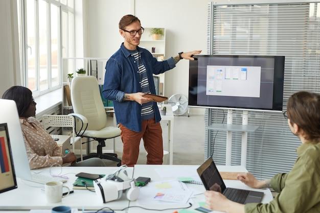 Vergadering van it-ontwikkelingsteam op kantoor met focus op getatoeëerde man die bij digitaal scherm staat en presentatie geeft, kopieerruimte