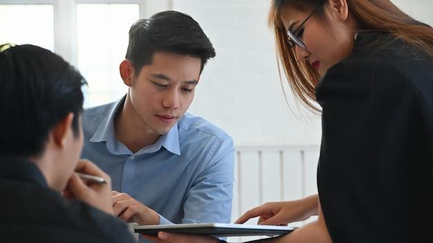 Vergadering van jonge zaken met close-up over het rapport van de zakenmanlezing in tabletcomputer.