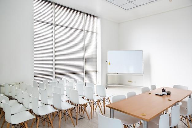 Vergaderruimte met een groot wit schoolbord en witte stoelen. leuke ruime kamer in een modern licht kantoor..