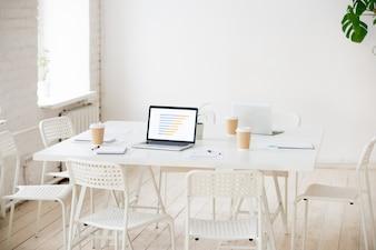 Vergadertafel met laptops en koffie in lege kantoorruimte