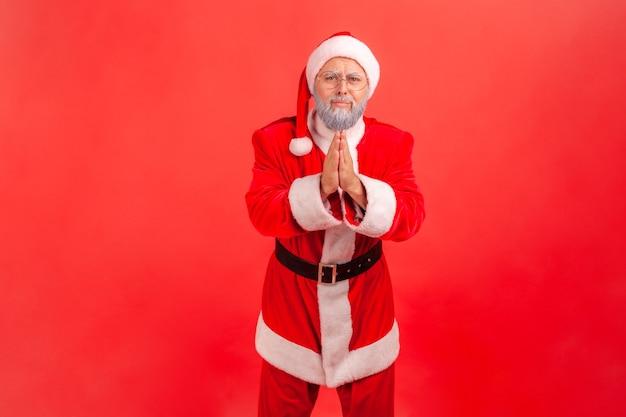 Vergeef me of geef me nog een kans. de kerstman staat met palmhanden, kijkt en smeekt.