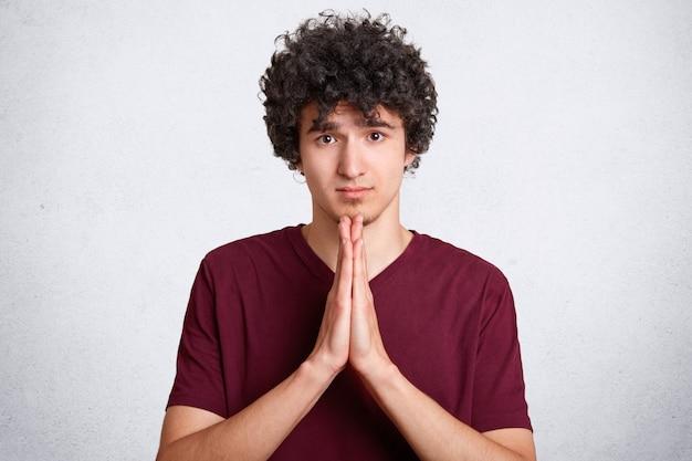 Vergeef mij alstublieft! het knappe jonge krullende mannetje maakt het bidden gebaar