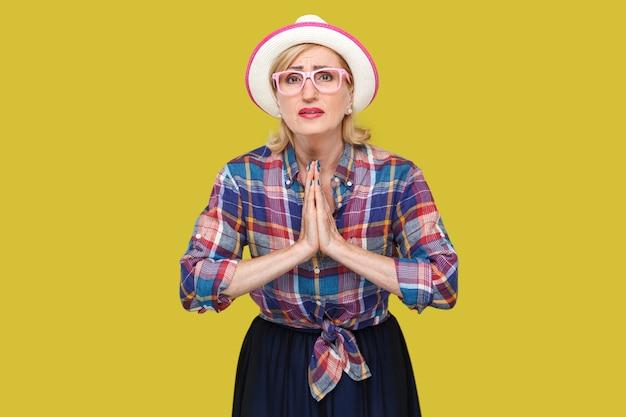 Vergeef mij alstublieft. of geef me nog een kans, portret van een hoopvolle volwassen vrouw in casual stijl met hoed en bril die met palmhanden staat en naar de camera kijkt, smeekt en vraagt. studio opname.