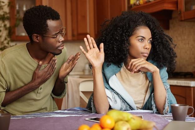 Vergeef mij alstublieft. ongelukkige afro-amerikaanse mannelijke cheater die hand op zijn borst houdt en zich verontschuldigt voor een mooie onverschillige vrouw die al zijn excuses negeert en weigert, en hem vertelt dat hij moet verdwalen
