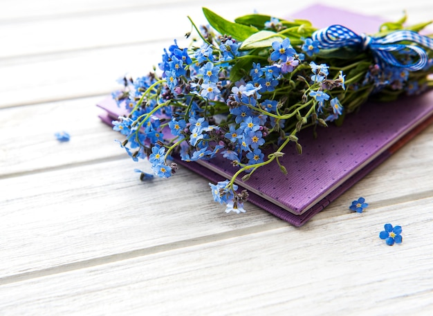 Vergeet me niet bloemen en notitieboekje op wit houten
