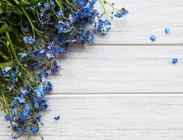 Vergeet-mij-nietjes op witte houten achtergrond met exemplaarruimte. romantiek concept.