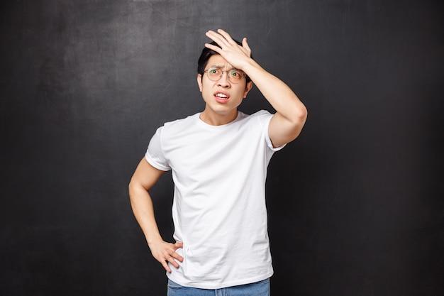 Vergeetachtig beschaamd jonge aziatische mannelijke student vergat een essay te schrijven voor de volgende klas, sloeg zichzelf op het voorhoofd en keek twijfelend met een gealarmeerde gehinderde uitdrukking, stond zwarte muur