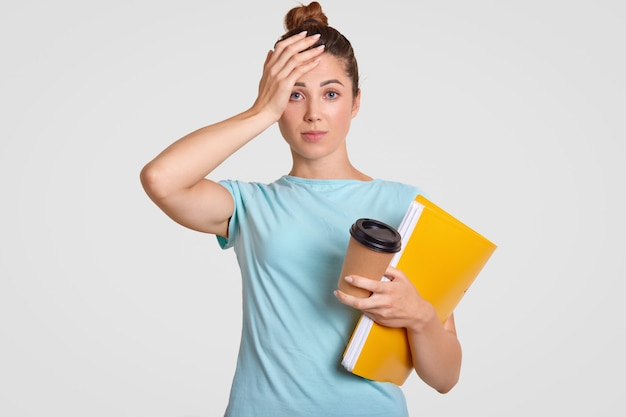 Vergeetachtige stressvolle student houdt de hand op het hoofd, gekleed in vrijetijdskleding, heeft een slecht geheugen, hoofdpijn na lang werken, heeft een deadline, bereidt zich voor op het komende examen, gebruikt wetenschappelijke literatuur
